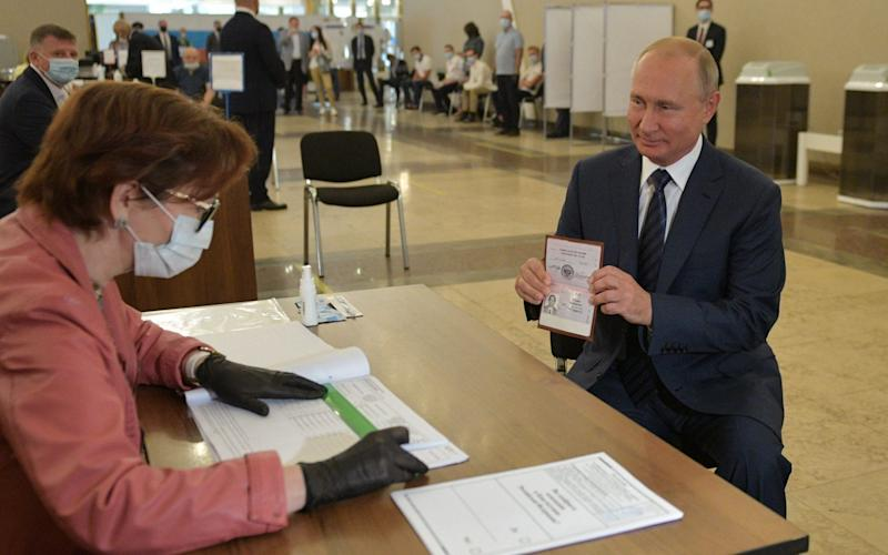 Vladimir Putin shows his ID to an election official before casting his ballot at a polling station in Moscow - Alexei Druzhinin/AFP