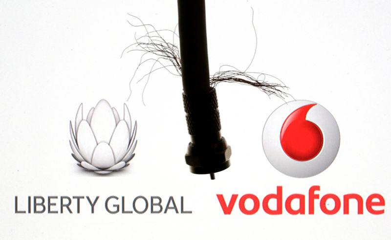 Coaxial TV Cable is seen in front of Vodafone and Liberty Global logos in this illustration