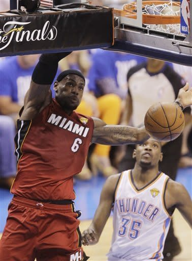 Miami Heat small forward LeBron James dunks against the Oklahoma City Thunder during the first half at Game 1 of the NBA finals basketball series, Tuesday, June 12, 2012, in Oklahoma City. At right is Thunder's Kevin Durant (35). (AP Photo/Sue Ogrocki)