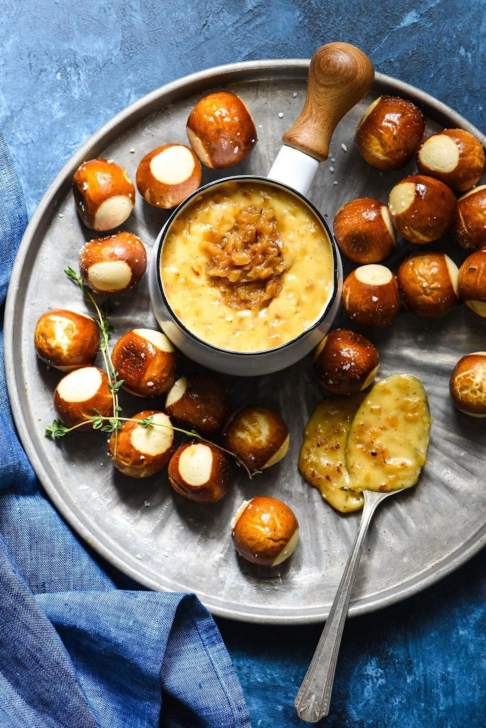 "<p>You heard it here first: three-cheese fondue is even better when you add deeply caramelized onions to the mix. Fontina, butterkase, and shredded grand cru cheese work together to make this the gooey dip of your dreams. Just add warm pretzel bites for best results.</p> <p><strong>Get the recipe</strong>: <a href=""https://foxeslovelemons.com/french-onion-cheese-fondue/"" class=""link rapid-noclick-resp"" rel=""nofollow noopener"" target=""_blank"" data-ylk=""slk:french onion cheese fondue"">french onion cheese fondue</a></p>"