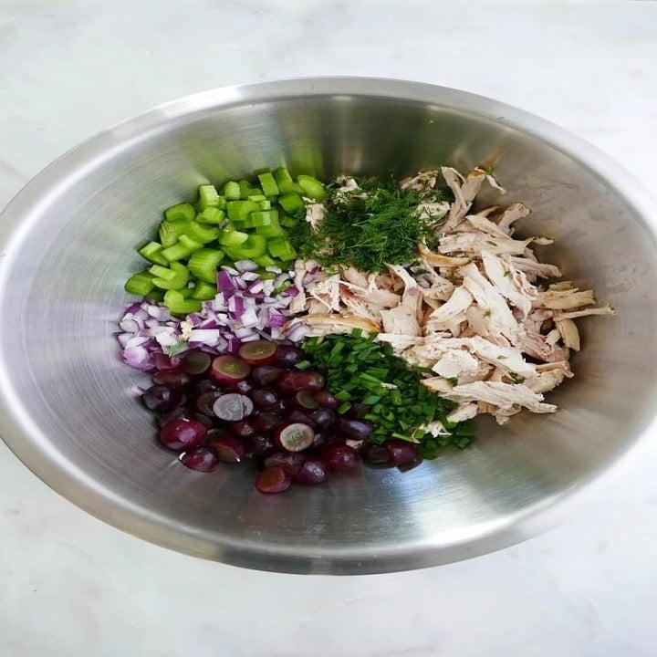 Ingredients for rotisserie chicken salad in a mixing bowl.