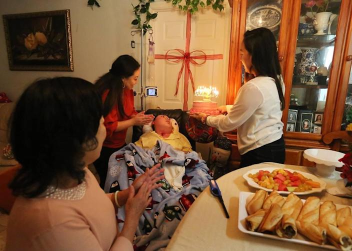 Justin Nguyen, 24, is cared for by his mother, Julie Nguyen, and his sisters, Jessica and Jennifer Pham, in their Jacksonville home. The family was celebrating Julie's birthday.