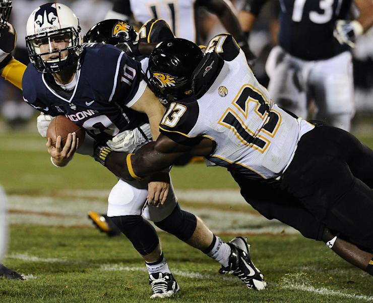 Connecticut quarterback Chandler Whitmer, left, is tackled by Towson's Greg Grant, back, and Towson's Telvion Clark, right, during the second half of an NCAA college football game at Rentschler Field in East Hartford, Conn., Thursday, Aug. 29, 2013. (AP Photo/Jessica Hill)