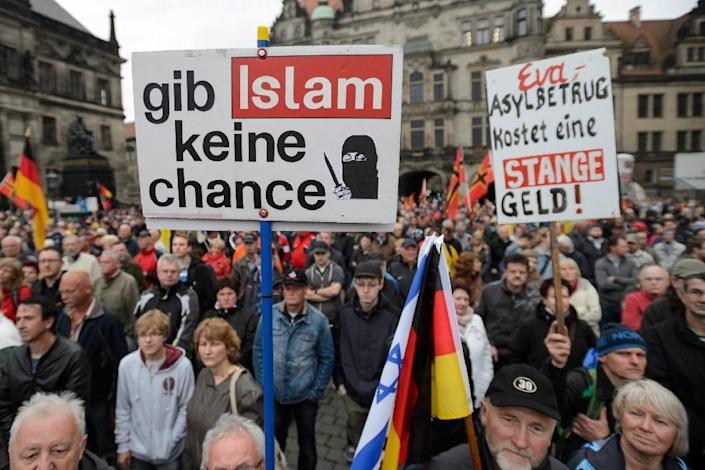 """Supporters of the German right-wing movement PEGIDA hold up a poster reading """"Give No Chance to Islam"""" as they attend a PEGIDA rally on June 1, 2015 in Dresden (AFP Photo/Jens Schlueter)"""