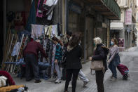 Women wearing protective face masks wait their turn outside a shop that sells yarns and fabrics central Athens, on Monday, April 5, 2021. Retail stores across most of Greece have been allowed to reopen despite an ongoing surge in COVID-19 infections, as the country battled to emerge from deep recession.(AP Photo/Petros Giannakouris)