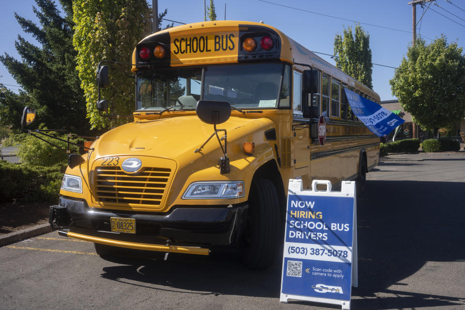 Lake Oswego, OR, USA - Sep 8, 2021: Now Hiring School Bus Drivers sign is seen next to an empty school bus operated by STA (Student Transportation of America) in Lake Oswego, Oregon.