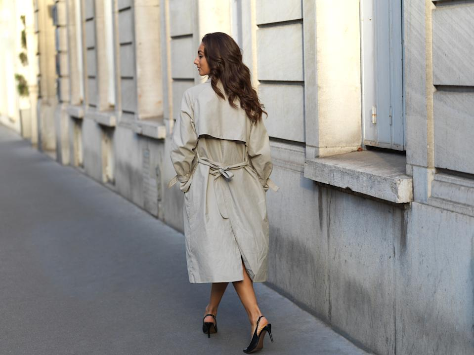 Stylish young woman wearing a trench coat, and high heels walking away from the camera on a sidewalk, street in Paris, France, on a beautiful bright sunny day