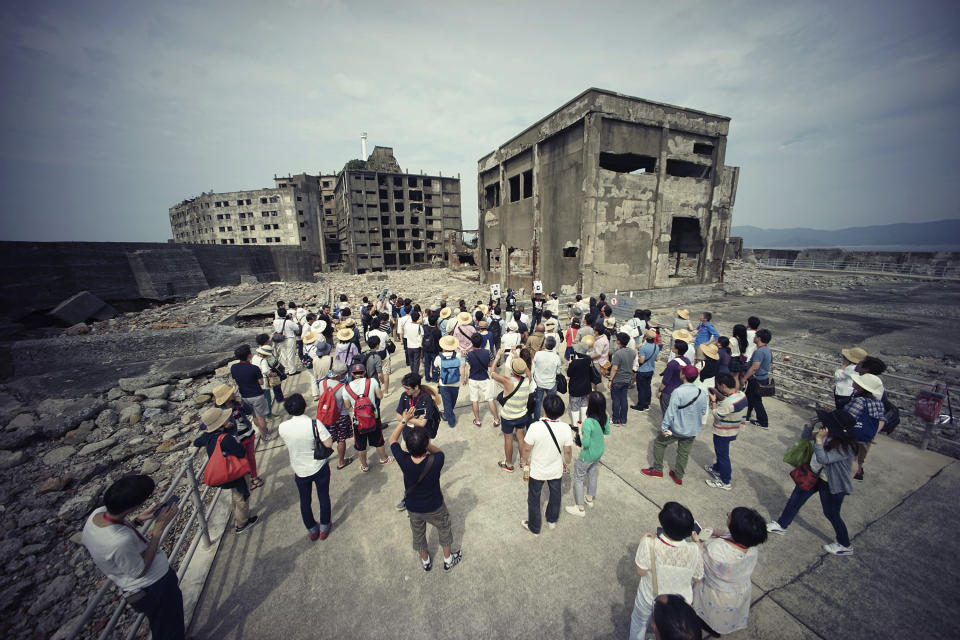 "FILE - In this June 29, 2015, file photo, tourists visit a part of Hashima Island, commonly known as Gunkanjima, which means ""Battleship Island,"" off Nagasaki, Nagasaki Prefecture, southern Japan. Gunkanjima was among the settings for a dark chapter in Japan's history, when hundreds of thousands of people were brought from the Korean Peninsula and other Asian nations to work in logging, in mines, on farms and in factories as forced labor. (AP Photo/Eugene Hoshiko, File)"