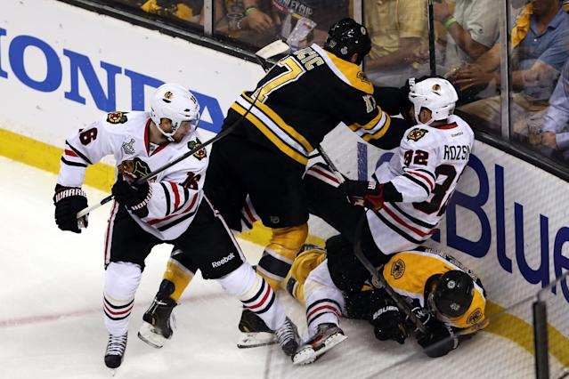 BOSTON, MA - JUNE 19: Milan Lucic #17 of the Boston Bruins hits Michal Rozsival #32 of the Chicago Blackhawks during the first period in Game Four of the 2013 NHL Stanley Cup Final at TD Garden on June 19, 2013 in Boston, Massachusetts. (Photo by Bruce Bennett/Getty Images)