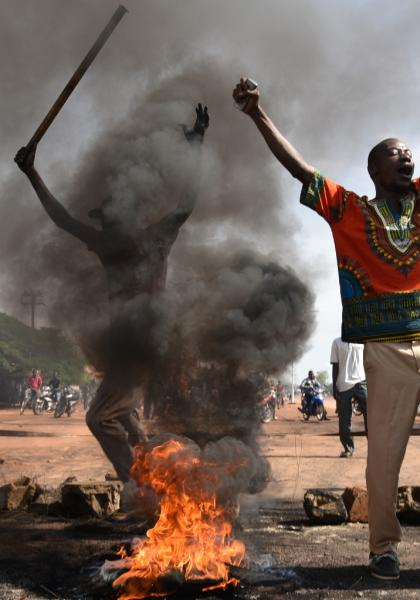 Demonstrators shout slogans next to burning tyres in the Tampouy neighbourhood of Ouagadougou during a protest against a regional proposal to end the crisis in Burkina Faso on September 21, 2015 (AFP Photo/Sia Kambou)