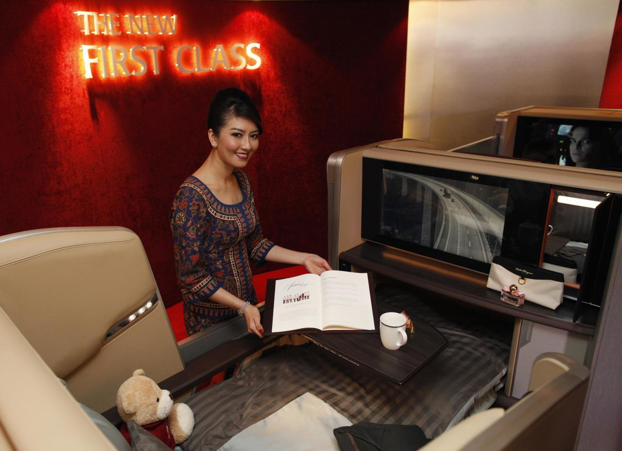 A Singapore Airlines Ltd stewardess poses at a first class cabin seat during the launch of their new generation of cabin products at Changi Airport in Singapore July 9, 2013. The new seats and in-flight entertainment system, an investment of nearly $150 million by the company, will be rolled out from September, starting with flights between Singapore and London on eight Boeing 777-300ER aircrafts. REUTERS/Edgar Su (SINGAPORE - Tags: TRANSPORT BUSINESS)