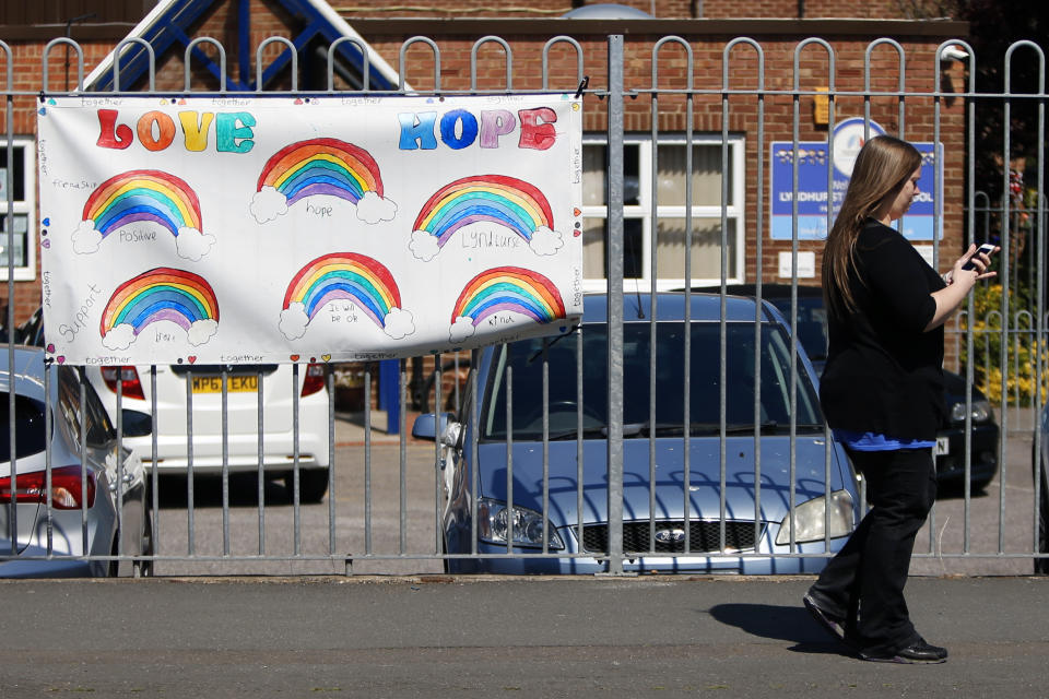 A woman walks past a rainbow banner on a school fence as the UK continues in lockdown to help curb the spread of coronavirus.
