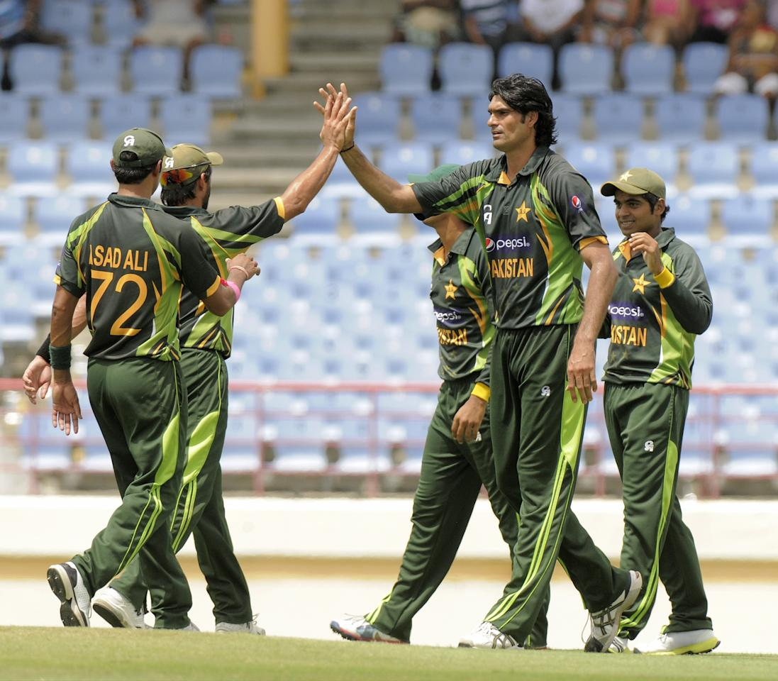 Pakistan bowler Mohammad Irfan (C) celebrates the dismissal of West Indies batsman Johnson Charles, caught Haris Sohail (R) during the 5th and final ODI West Indies v Pakistan on July 24, 2013 at Beausejour Cricket Ground, in Gros Islet, St. Lucia. The score was , WI 111/3 (29 ov)KS. AFP PHOTO/RANDY BROOKS        (Photo credit should read RANDY BROOKS/AFP/Getty Images)