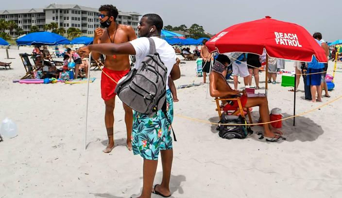 A beachgoer asks a Shore Beach Service lifeguard about a rental on Saturday, June 27, 2020 on the beach of Hilton Head Island. Lifeguards must wear a face covering while on the beach and they maintain social distancing by marking off their lifeguard stands with a boundary rope.