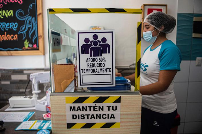 """An employee stands next to a sign reading """"Temporarily reduced capacity 50%"""" at a restaurant in Lima on July 20, 2020. <p class=""""copyright"""">ERNESTO BENAVIDES/AFP via Getty Images</p>"""