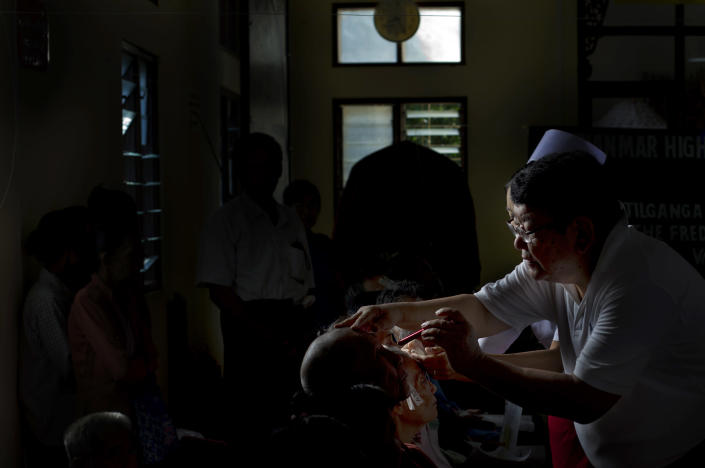 In this Oct. 23, 2013 photo, Surgeon Sandut Ruit, inspects an eye of a patient a day after they underwent a simple operation to remove a cataract, in Bago, Myanmar. Ruit, who helped pioneer the technique, oversaw nearly 1,300 operations at two massive eye camps in 10 days earlier this month (October) as dozens of local ophthalmologists looked on. (AP Photo/Gemunu Amarasinghe)