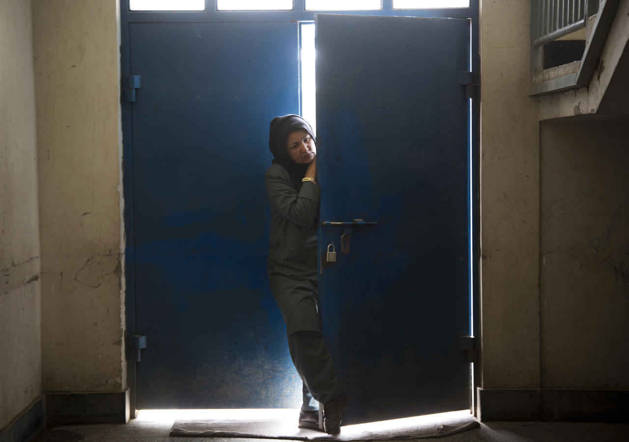 """Picture taken March 28, 2013 shows an Afghan female guard peering through the main gate at Badam Bagh, Afghanistan's central women's prison, in Kabul, Afghanistan. 202 women living in the six- year- old jail, the majority of the women are serving sentences of up to seven years for leaving their husbands, refusing to accept a marriage arranged by their parents, or choosing to leave their parent's home with a man of their choice, all so-called """"moral"""" crimes(. AP Photo/Anja Niedringhaus)"""