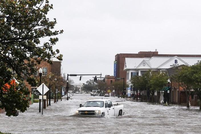 A city worker drives through a flooded street in Pensacola, Florida, after Hurricane Sally