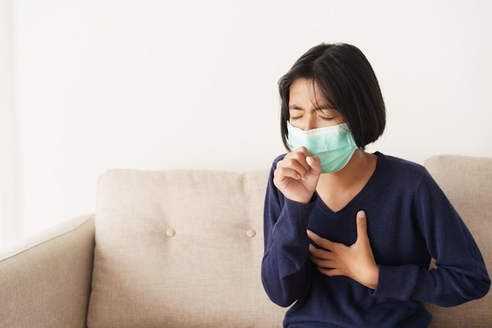 girl symptom cough and are protective with medical mask while sitting on sofa, Asia child wearing a protection mask epidemic of flu or covid-19 in living room at home. Health and illness concept