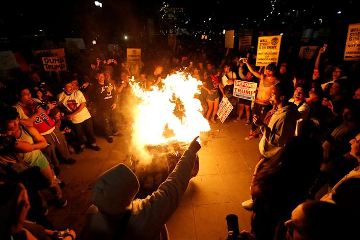 <p>A Donald Trump pinata is burned by people protesting the election of Republican Donald Trump as the president of the United States in downtown Los Angeles, Calif., Nov. 9, 2016. (Photo: Mario Anzuoni/Reuters) </p>