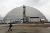 A man walks past a shelter covering the exploded reactor at the Chernobyl nuclear plant, in Chernobyl, Ukraine, Thursday, April 15, 2021. The vast and empty Chernobyl Exclusion Zone around the site of the world's worst nuclear accident is a baleful monument to human mistakes. Yet 35 years after a power plant reactor exploded, Ukrainians also look to it for inspiration, solace and income. (AP Photo/Efrem Lukatsky)