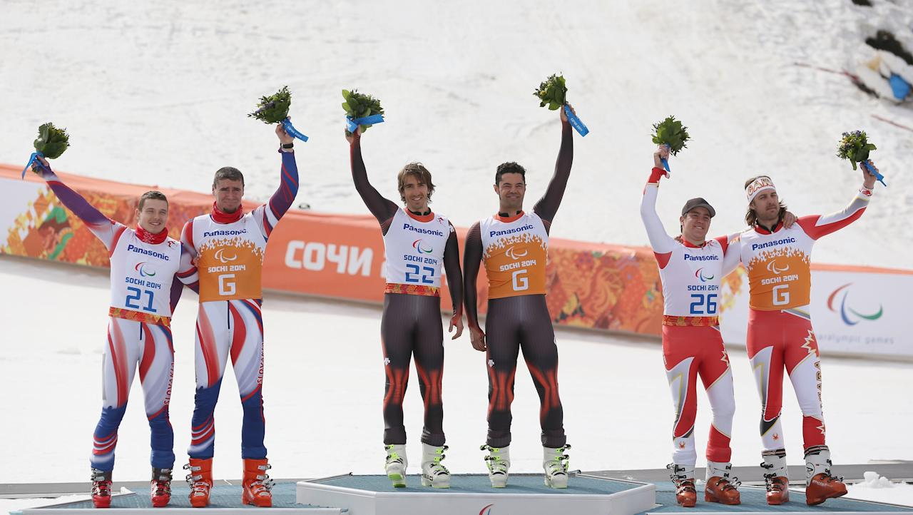 SOCHI, RUSSIA - MARCH 08: Silver medalist's Miroslav Haraus and guide Maros Hudik of Slovakia, gold medalist's Yon Santacana Maiztegui and guide Miguel Galindo Garces, and bronze medalist's Mac Marcoux and Guide Robin Femy of Canada celebrate during the flower ceremony following the Mens Downhill Visually Impaird during day one of Sochi 2014 Paralympic Winter Games at Rosa Khutor Alpine Center on March 8, 2014 in Sochi, Russia. (Photo by Ian Walton/Getty Images)