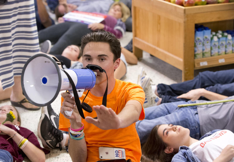 "Marjorie Stoneman Douglas High School student David Hogg speaks as demonstrators lie on the floor at a Publix Supermarket in Coral Springs, Fla., Friday, May 25, 2018. Students from the Florida high school where 17 people were shot and killed earlier this year did a ""die in"" protest at a supermarket chain that backs a gubernatorial candidate allied with the National Rifle Association. Shortly before the the ""die-in"" Publix announced that it will suspend political donations. (AP Photo/Wilfredo Lee)"