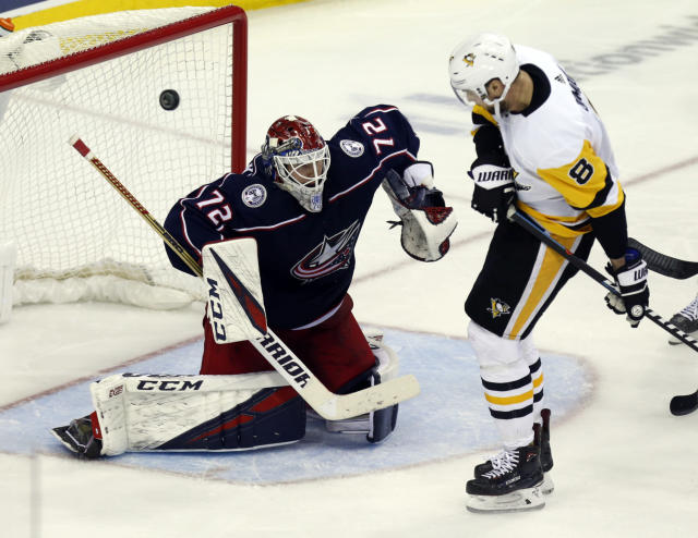 Columbus Blue Jackets goalie Sergei Bobrovsky, left, of Russia, makes a stop against Pittsburgh Penguins defenseman Brian Dumoulin during the third period of an NHL hockey game in Columbus, Ohio, Saturday, March 9, 2019. (AP Photo/Paul Vernon)