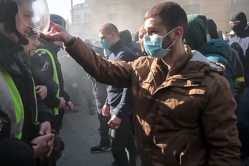 In this image from video provided Radio Free Europe/Radio Liberty, far-right demonstrators clash with riot police outside the presidential administration building in Kiev, Ukraine, Saturday, March 9, 2012. Three police officers in Ukraine have been injured in a clash with far-right demonstrators in the capital. The violence occurred outside the presidential administration building in Kiev where several hundred demonstrators had gathered Saturday to call for arrests of top figures in an alleged military corruption scandal. (Radio Free Europe/Radio Liberty via AP)