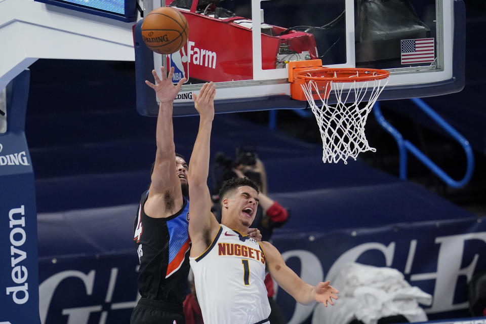 Oklahoma City Thunder guard Kenrich Williams, left, fouls Denver Nuggets forward Michael Porter Jr. (1) during the first half of an NBA basketball game Saturday, Feb. 27, 2021, in Oklahoma City. (AP Photo/Sue Ogrocki)