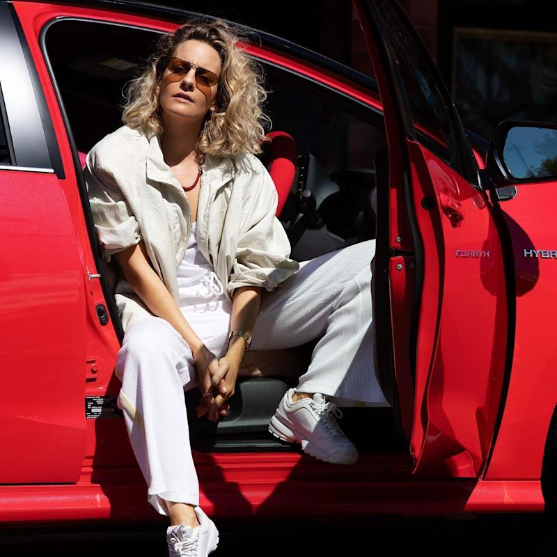 Designer and founder of Australian activewear brand First Base Alison Cotton sitting in the front seat of a red Toyota Yaris