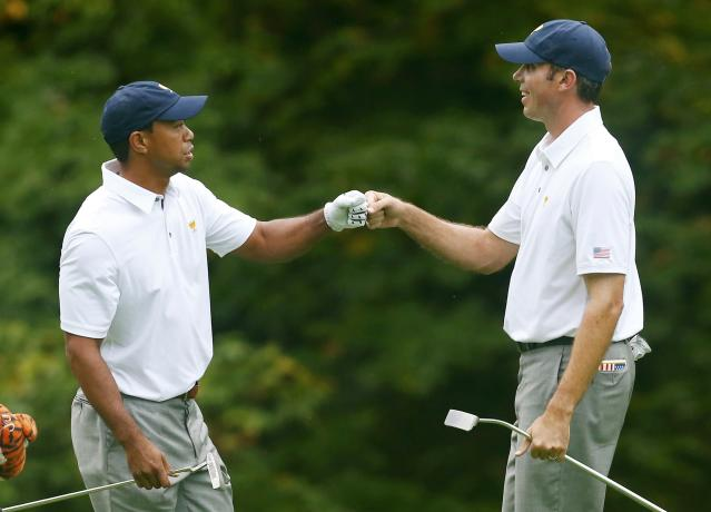 U.S. golfer Tiger Woods (L) celebrates his approach shot on the 15th green with teammate Matt Kuchar as they play the International team of Ernie Els and Brendon de Jonge during the continuation of the rain delayed Foursome matches for the 2013 Presidents Cup golf tournament at Muirfield Village Golf Club in Dublin, Ohio October 6, 2013. REUTERS/Chris Keane (UNITED STATES - Tags: SPORT GOLF)