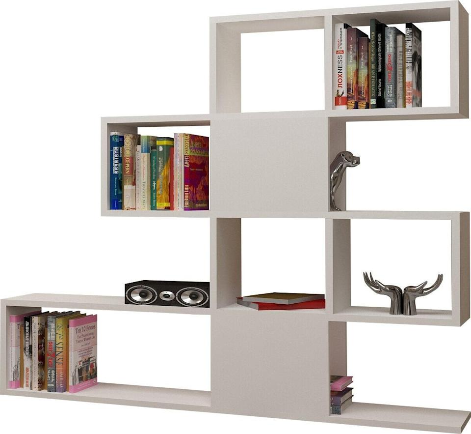 """<h2>Dakota 43'' H x 47'' W Geometric Bookcase</h2><br><strong>Deal: 16% off<br></strong>We think this new wave bookcase is perfect if your bedroom happens to also be your living room. When small spaces don't leave room for walls, create your own boundaries by sectioning off the room with a sturdy bookcase unit that offers stylish geometric separation.<br><br><em>Shop</em> <strong><em><a href=""""https://www.wayfair.com/brand/bnd/hashtag-home-b50028.html"""" rel=""""nofollow noopener"""" target=""""_blank"""" data-ylk=""""slk:Hashtag Home"""" class=""""link rapid-noclick-resp"""">Hashtag Home</a></em></strong><br><br><br><strong>Hashtag Home</strong> Dakota 43'' H x 47'' W Geometric Bookcase, $, available at <a href=""""https://go.skimresources.com/?id=30283X879131&url=https%3A%2F%2Fwww.wayfair.com%2Ffurniture%2Fpdp%2Fhashtag-home-dakota-43-h-x-47-w-geometric-bookcase-w001787825.html"""" rel=""""nofollow noopener"""" target=""""_blank"""" data-ylk=""""slk:Wayfair"""" class=""""link rapid-noclick-resp"""">Wayfair</a>"""