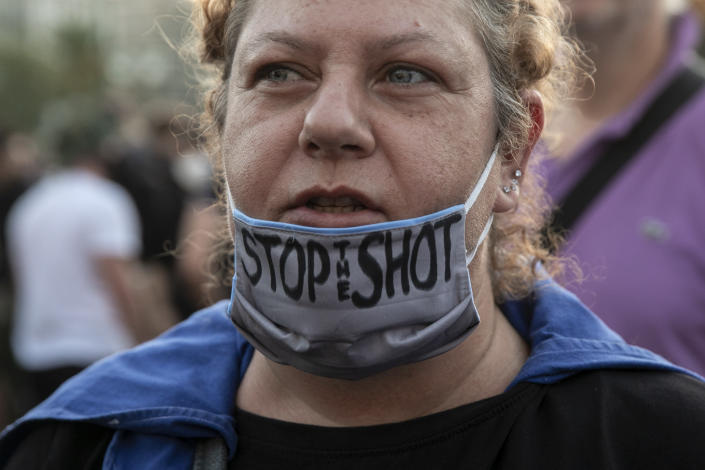 An anti-vaccine protester shouts slogans during a rally at central Syntagma square, in Athens, Greece, Sunday, Aug. 29, 2021. Police used tear gas to disperse thousands of protesters opposing government's plans for mandatory vaccination and new testing requirements and attendance restrictions on people who aren't vaccinated against COVID-19. (AP Photo/Yorgos Karahalis)