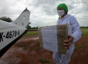 Bacteriologist Diana Carolina Galvan from the Hospital de La Primavera using protection elements carries a box with samples of the coronavirus disease (COVID-19) that will be processed in Bogota, in La Primavera