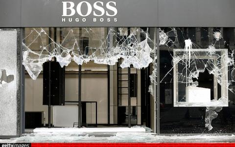 The vandalized facade of the Hugo Boss shop is seen after the 18th consecutive Saturday of demonstrations - Credit: Getty Images Europe