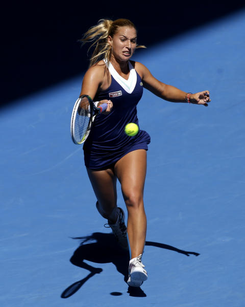 Dominika Cibulkova of Slovakia makes a forehand return to Simona Halep of Romania during their quarterfinal at the Australian Open tennis championship in Melbourne, Australia, Wednesday, Jan. 22, 2014.(AP Photo/Aijaz Rahi)