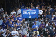 Fans hold up a banner and cheer after Los Angeles Dodgers' Chris Taylor hit a three-run home run off Colorado Rockies starting pitcher Chi Chi Gonzalez during the first inning of a baseball game Friday, July 16, 2021, in Denver. (AP Photo/David Zalubowski)