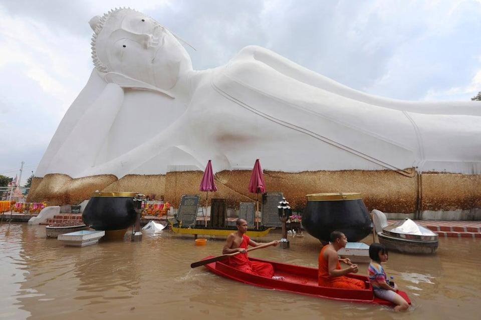 Buddhist monks paddle a boat through floodwaters in front of a reclining Buddha at the Wat Satue in Ayutthaya province. (AP)