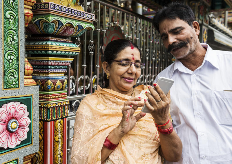 Indian woman using a smartphone while a man looks at the screen