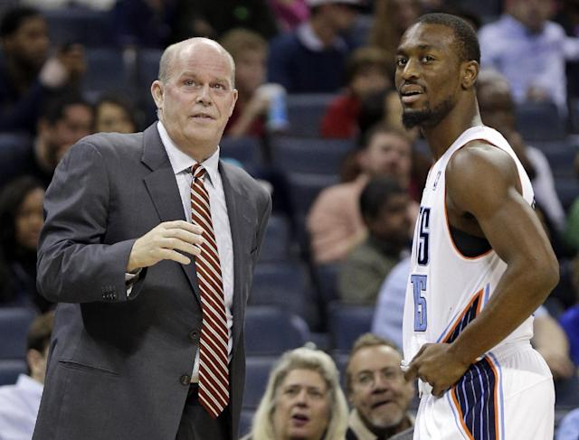 Charlotte Bobcats head coach Steve Clifford, left, talks with Kemba Walker, right, during the first half of an NBA basketball game against the Phoenix Suns in Charlotte, N.C., Friday, Nov. 22, 2013. (AP Photo/Chuck Burton)