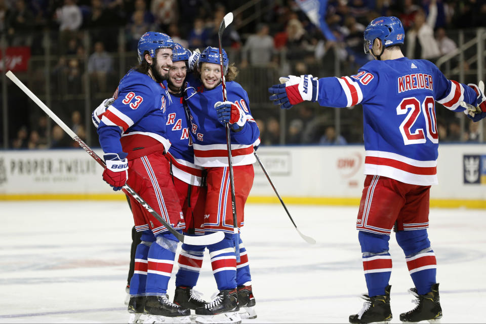 New York Rangers center Mika Zibanejad (93), defenseman Tony DeAngelo (77) and and left wing Artemi Panarin (10) embrace while celebrating DeAngelo's third goal as Rangers left wing Chris Kreider (20) approaches the group during the second period of an NHL hockey game against the New Jersey Devils, Thursday, Jan. 9, 2020, in New York. (AP Photo/Kathy Willens)