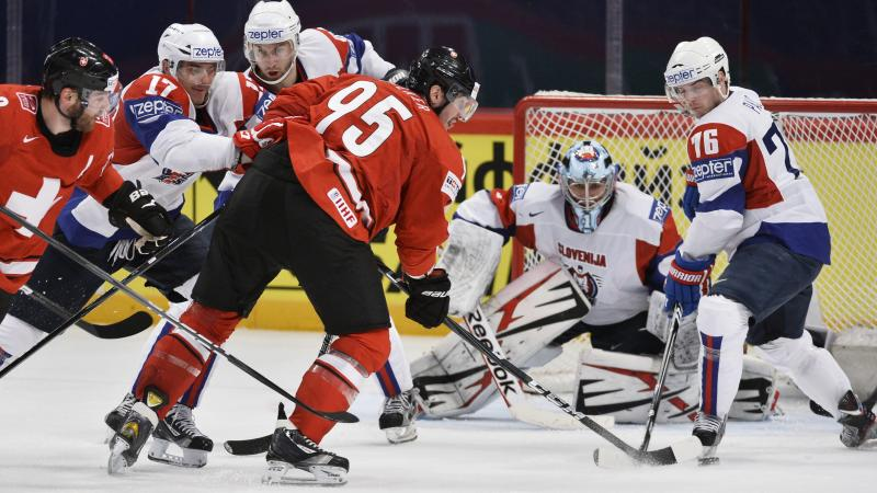 Switzerland's Simon Moser, center, scores the 5-1 goal against Slovenia during the Ice Hockey World Championship group A match in Stockholm, Sweden, Tuesday May 8, 2013. (AP Photo/Anders Wiklund/Scanpix) SWEDEN OUT