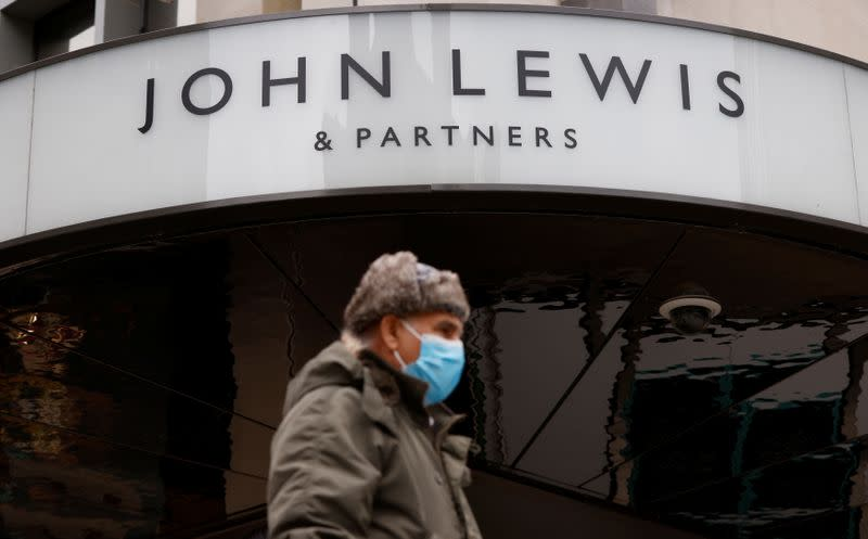 A man wearing a face mask walks past a temporarily closed John Lewis department store on Oxford Street in London,