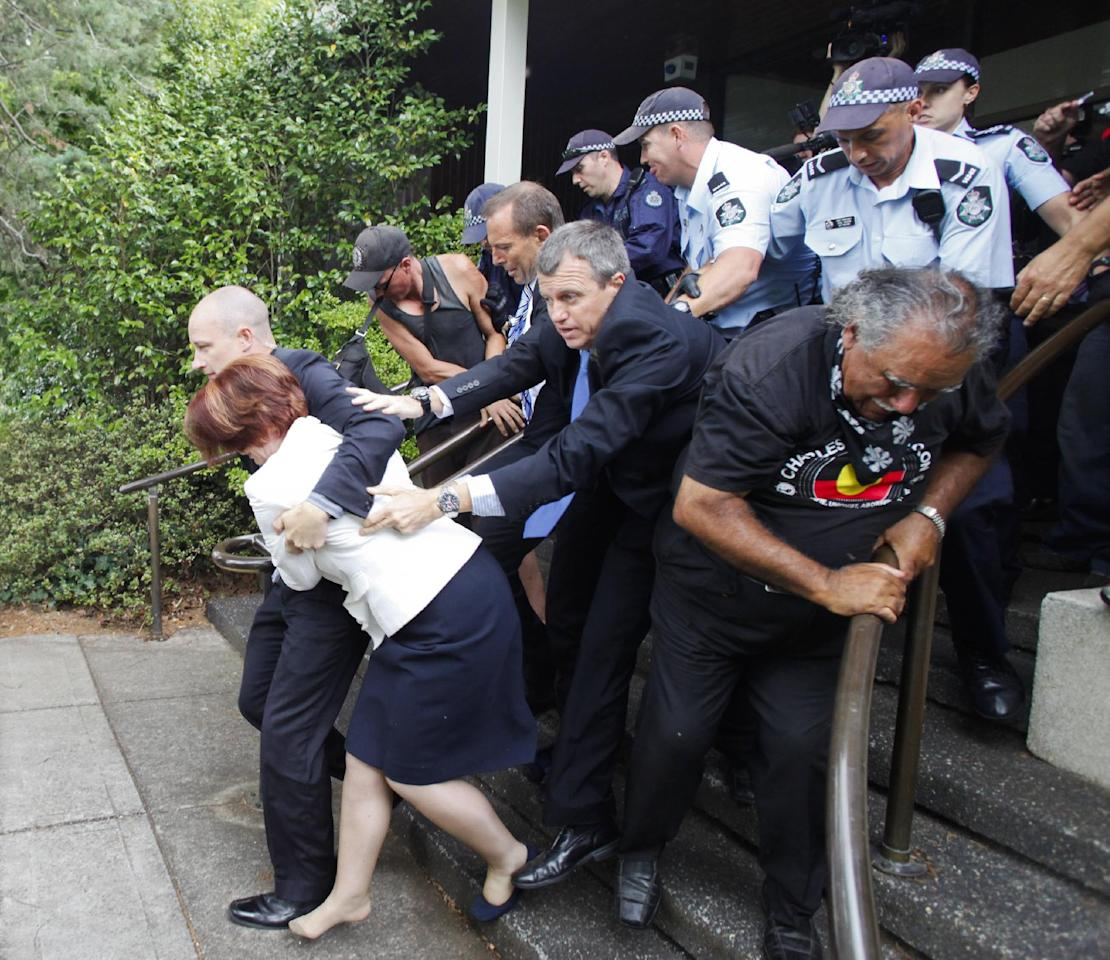 Prime Minister Julia Gillard is escorted out for safety by body guards and police through a crowd of rowdy protesters following a ceremony to mark Australia's national day in Canberra, Australia, Thursday Jan. 26, 2012. Some 200 supporters of indigenous rights surrounded a Canberra restaurant and banged its windows on Thursday while Gillard and opposition leader Tony Abbott were inside officiating at an award ceremony. (AP Photo/Lukas Coch) AUSTRALIA OUT