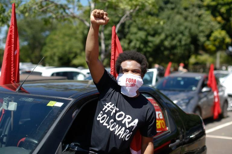 Protesters in this caravan in Brasilia on January 23, 2021 demanded the ouster of President Jair Bolsonaro over his handling of the pandemic; this man's T-shirt reads 'Bolsonaro Out'