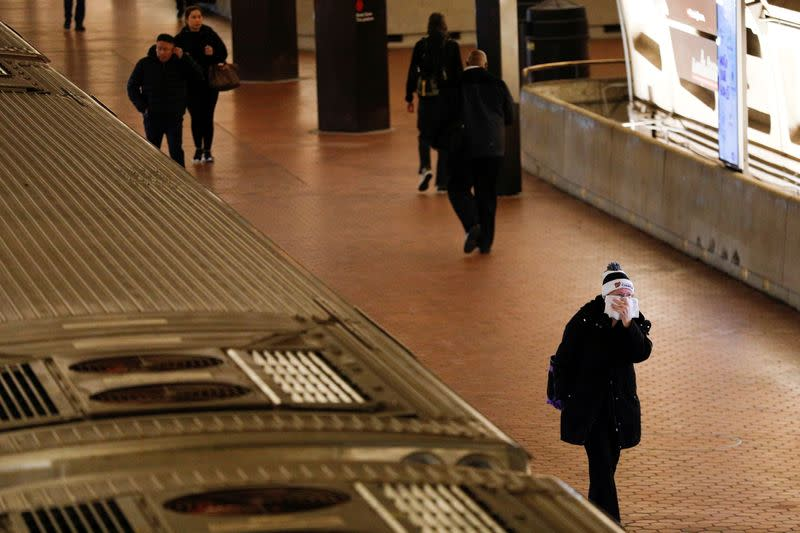 FILE PHOTO: A morning commuter holds a towel covering a face after departing from a Metro train car, as Mayor Muriel Bowser declared a State of Emergency due to the coronavirus disease (COVID-19), inside the Metro Center underground subway station, in Wash
