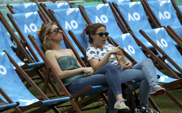 Spectators wait for play to start in Garden Square ahead of the first round singles matches at the Australian Open tennis championship in Melbourne, Australia, Monday, Jan. 20, 2020. (AP Photo/Dita Alangkara)