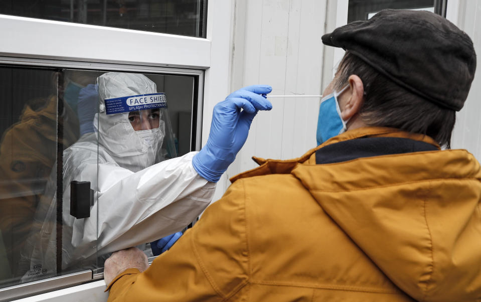 Medical staff takes a COVID-19 test at a coronavirus test center in Cologne, Germany, Thursday, Oct. 15, 2020. The city exceeded the important warning level of 50 new infections per 100,000 inhabitants in seven days. More and more German cities become official high risk corona hotspots with travel restrictions within Germany. (AP Photo/Martin Meissner)