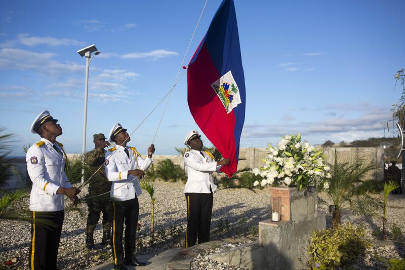 National police officers raise a Haitian national flag during a memorial service honoring the victims of the 2010 earthquake, at Titanyen, a mass burial site north of Port-au-Prince, Haiti, Friday, Jan. 12, 2018. Haitians reacted with outrage Friday to reports that President Donald Trump used a vulgar remark to describe the country on the eve of the anniversary of the 2010 earthquake, one of the deadliest disasters in modern history. (AP Photo/Dieu Nalio Chery)